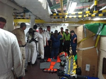 A medical equipment on standby and the medical officers giving instruction to the stretcher bearers.